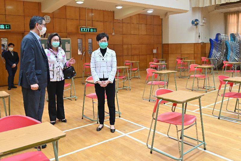 行政長官林鄭月娥今日(三月二十三日)到訪位於將軍澳的仁濟醫院王華湘中學,了解該校師生在停課期間透過電子學習的情況,並感謝教職員在疫情下致力支援學生在家中持續學習。圖示林鄭月娥(右)參觀準備作為香港中學文憑考試試場的學校禮堂。