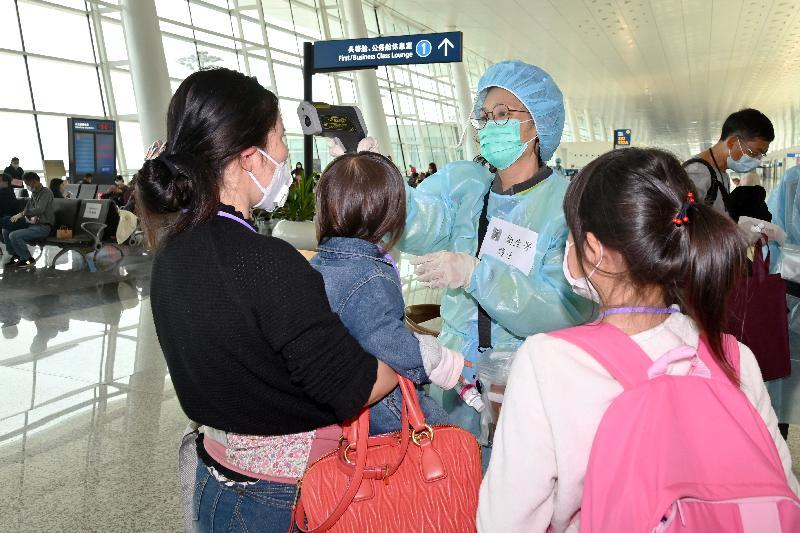 衞生署護士今日(三月二十五日)在武漢天河國際機場的候機區,為滯留湖北省的香港家庭量度體溫。