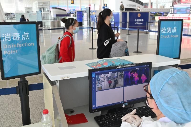 特區政府今日(三月二十五日)安排第二批專機,接載滯留在湖北省的香港居民回港。圖示乘坐今日第二架專機的香港居民在進入武漢天河國際機場前接受紅外線體溫探測。
