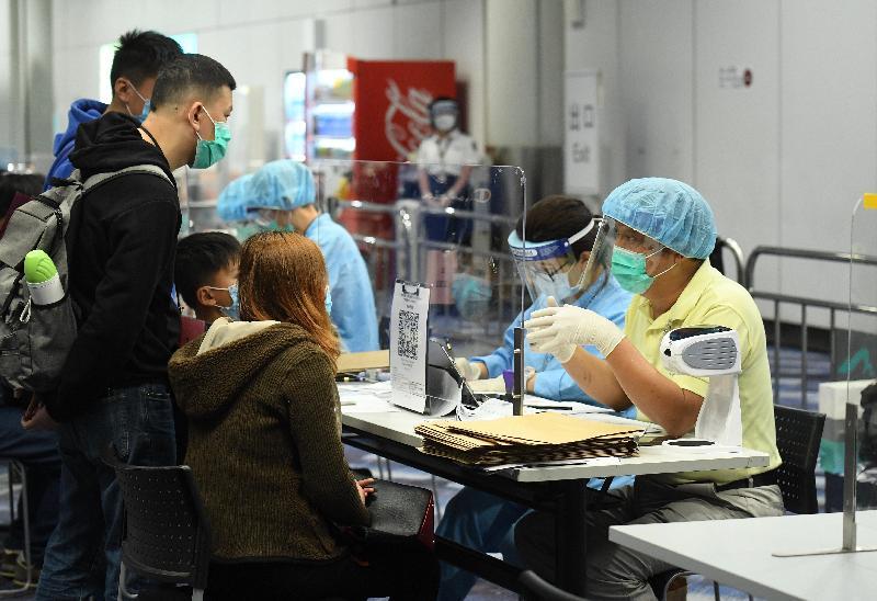 特區政府今日(三月二十五日)安排第二批專機,接載滯留在湖北省的香港居民回港。圖示乘坐專機的香港居民抵港後聽取衞生署人員講解強制檢疫安排。