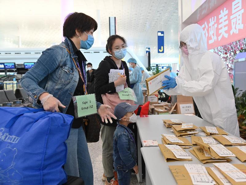 航空公司職員今日(三月二十六日)在武漢天河國際機場向乘搭專機的香港居民派發機票。