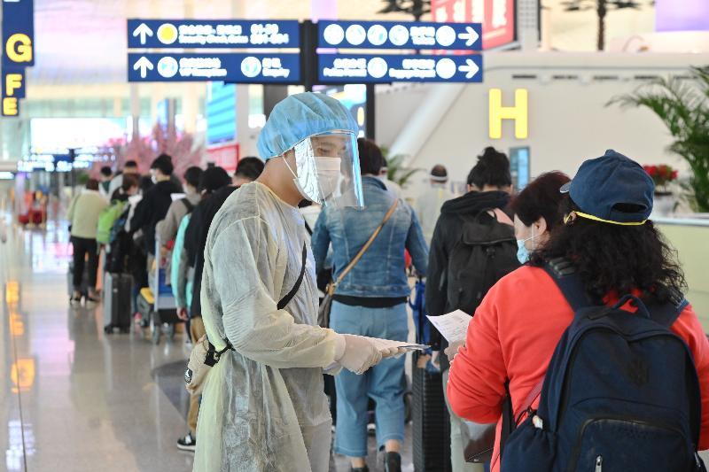 香港特區政府今日(三月二十六日)繼續派出第二批專機接載滯留在湖北省的香港居民回港。圖示入境處職員在武漢天河國際機場向乘搭專機的香港居民派發健康申報表。