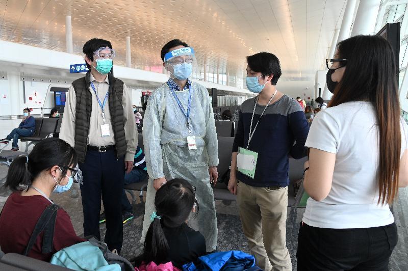 政制及內地事務局局長聶德權(左二)與駐武漢經濟貿易辦事處主任馮浩賢(左一)今日(三月二十六日)在武漢天河國際機場,與正在等候上機的一個來自恩施的家庭交談,並向他們致以問候。