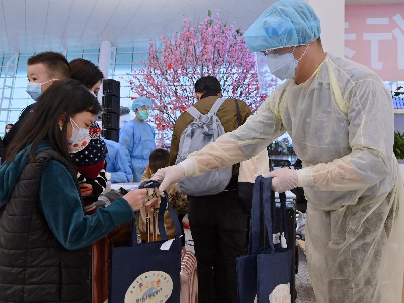 入境事務處人員今日(三月二十六日)在武漢天河國際機場向乘搭專機回港滯留在湖北省的港人派發禮物包,當中包括酒精搓手液、口罩及健康須知。