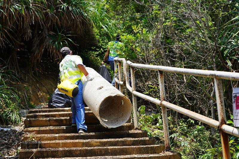 多個政府部門聯同一眾義工今日(四月二十七日)在塔門弓背灣進行聯合淨灘行動。圖示食物環境衞生署人員徒步運送包好的垃圾到臨時存放點。