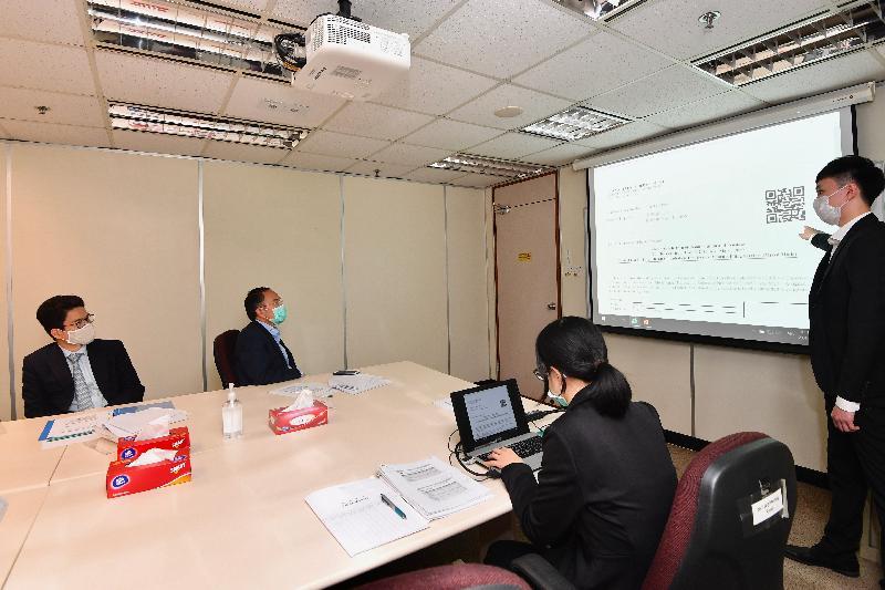 財經事務及庫務局局長許正宇今日(五月二十一日)到訪稅務局。圖示許正宇(左二)聽取該局人員介紹處理僱主電子報税服務的流程。
