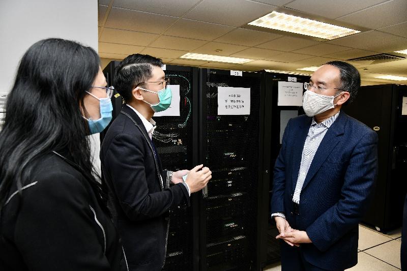 財經事務及庫務局局長許正宇今日(五月二十八日)到訪差餉物業估價署。圖示許正宇(右一)聽取電腦科同事介紹該署的電子系統。