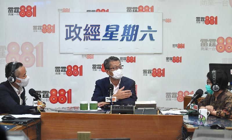 財政司司長陳茂波(中)今日(六月十三日)上午出席商業電台節目「政經星期六」。