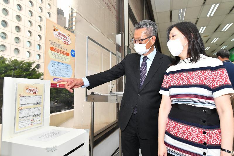 財政司司長陳茂波(左)今日(六月二十六日)在郵政署署長朱曼鈴(右)陪同下參觀香港郵政中環郵政總局,了解香港郵政協助推行現金發放計劃的相關工作。