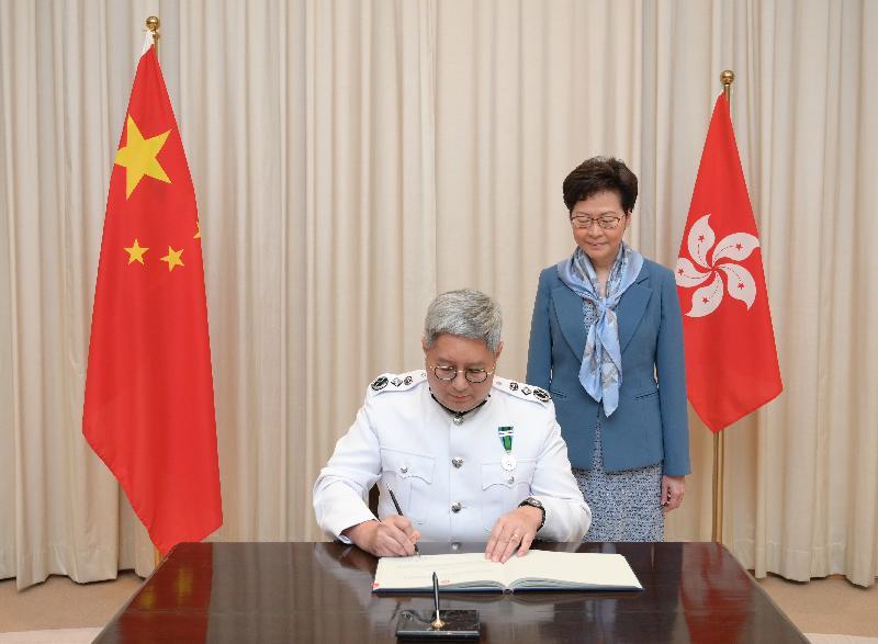 新任入境事務處處長區嘉宏(左)今日(七月二日)在宣誓後簽署誓言。