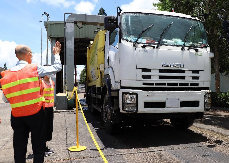 環境局局長黃錦星今日(七月二十三日)到訪北大嶼山廢物轉運站,視察環境保護署向使用轉運站的廢物運輸車輛司機派送口罩及相關運作情況。圖示黃錦星(左)向廢物運輸車輛司機致意,感謝他們緊守崗位,同心抗疫。