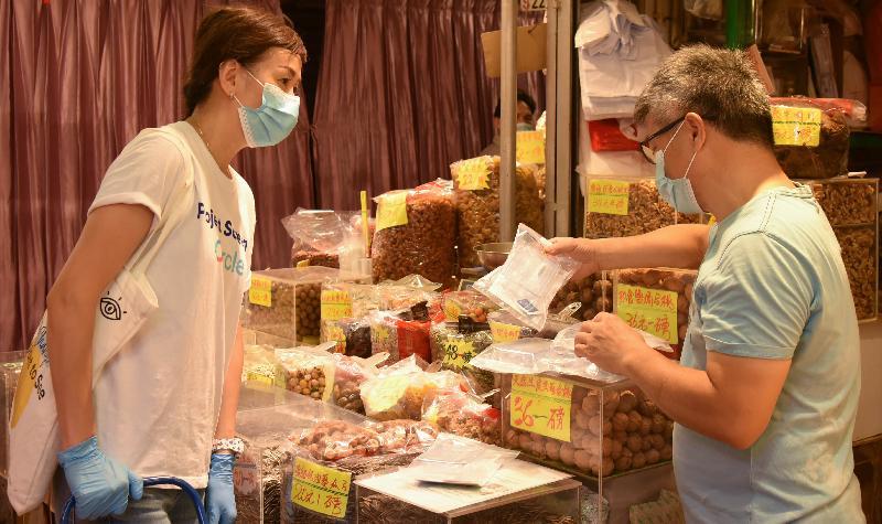 食物環境衞生署今日(七月二十八日)開始為街市攤檔從業員安排2019冠狀病毒病檢測服務。圖示檢測承辦商派發樣本瓶予攤檔從業員收集深喉唾液樣本進行檢測。