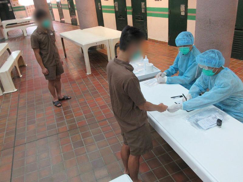 懲教署本星期為在囚人士進行2019冠狀病毒病測試,並於今日(九月十一日)公布結果全屬陰性。圖示懲教人員為男性在囚人士安排病毒測試。