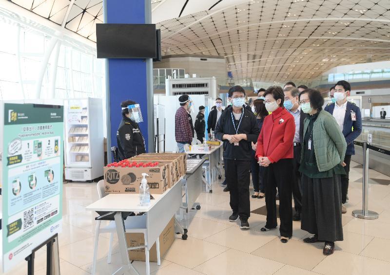 行政長官林鄭月娥(前排中)今日(十二月二十六日)到香港國際機場中場客運大樓,檢視各部門落實執行對抵港人士實施的檢疫措施。