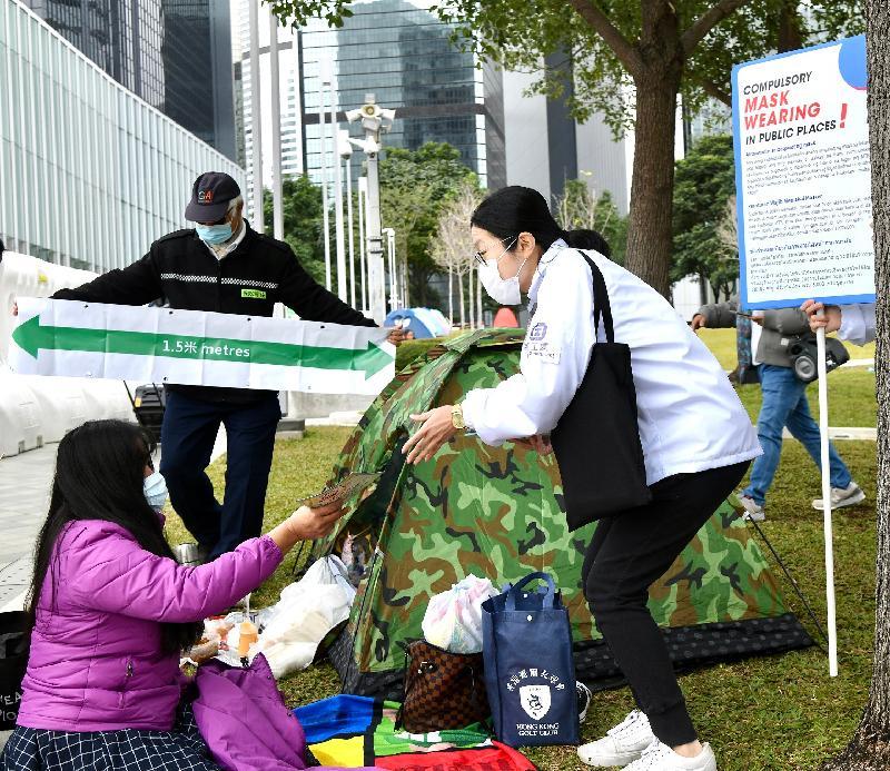勞工處今日(一月十日)聯同香港警務處、食物環境衛生署、民政事務總署及康樂及文化事務署在外籍家庭傭工(外傭)經常聚集的地方採取聯合行動,包括透過流動廣播宣傳,呼籲他/她們遵守有關佩戴口罩及禁止於公眾地方兩人以上的羣組聚集等防疫規例。圖示勞工處在金鐘添馬公園向外傭派發宣傳單張。