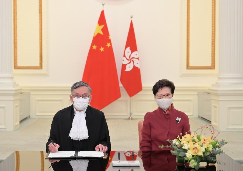 終審法院首席法官張舉能(左)今日(一月十一日)在宣誓後簽署司法誓言。