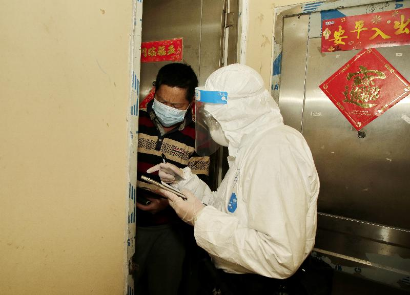 The Sham Shui Po District Office, the Sham Shui Po Police District and the Auxiliary Medical Service conducted enforcement action on compulsory testing notices today (January 29) at six buildings in Sham Shui Po, which were included in the compulsory testing notices earlier. Photo shows Government staff members conducting a home visit at a building for random checking on whether residents have undergone testing.