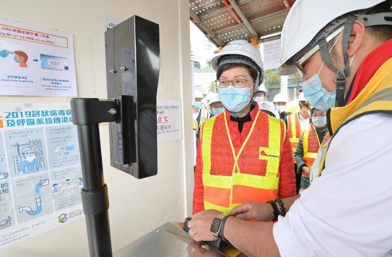 行政長官林鄭月娥今日(二月十一日)到訪西九文化區M+博物館工地,視察工地內推行的防疫措施。圖示林鄭月娥(左)在進入工地前接受體溫監測。