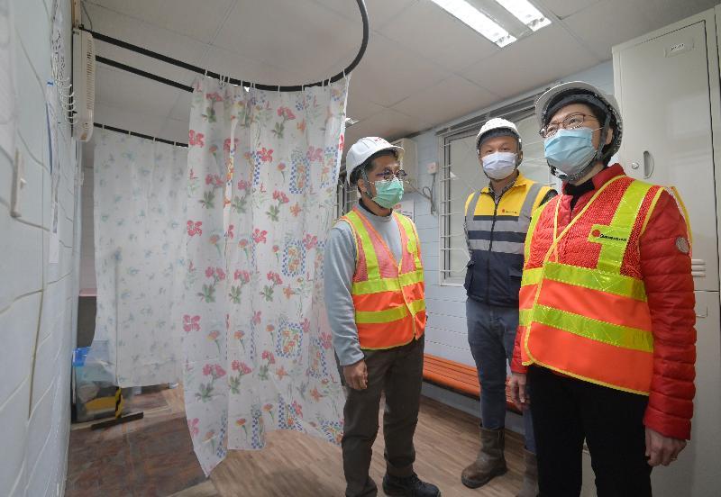 行政長官林鄭月娥今日(二月十一日)到訪西九文化區M+博物館工地,視察工地內推行的防疫措施。圖示林鄭月娥(右)參觀員工更衣室,了解該處的防疫措施。