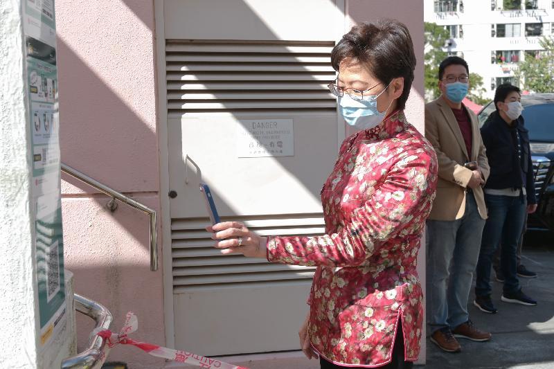 行政長官林鄭月娥今日(二月十二日)到訪設於荔景社區會堂的社區檢測中心。圖示林鄭月娥進入社區檢測中心前掃描「安心出行」應用程式二維碼。