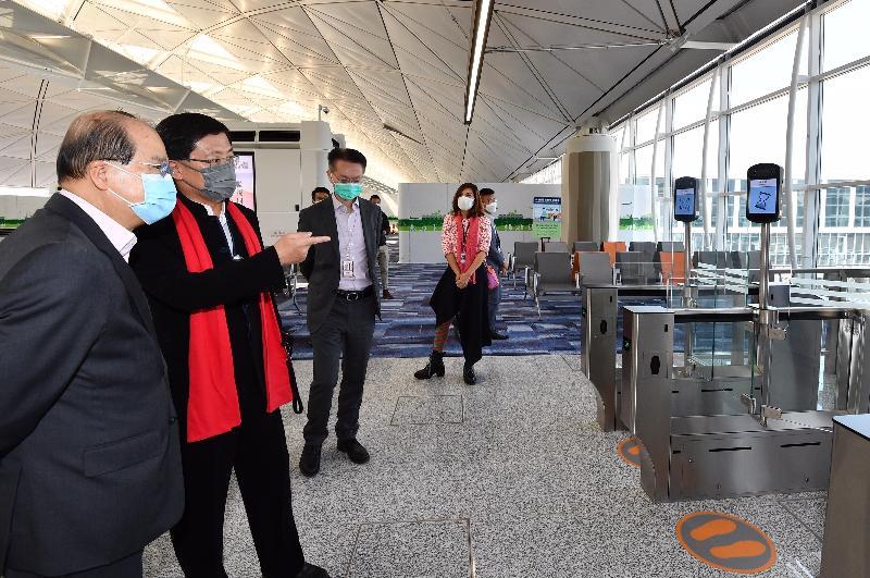 政務司司長張建宗今日(二月十三日)到訪香港國際機場。圖示張建宗(左一)聽取機場管理局行政總裁林天福(左二)簡介登機閘口翻新工程的最新進展。