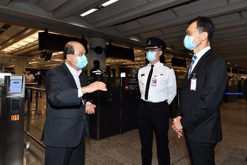 政務司司長張建宗今日(二月十三日)到訪香港國際機場。圖示張建宗(左一)在入境事務處副處長陳天賜(右一)陪同下,與當值的入境事務處前線人員交談,感謝他們在假期期間辛勤工作。
