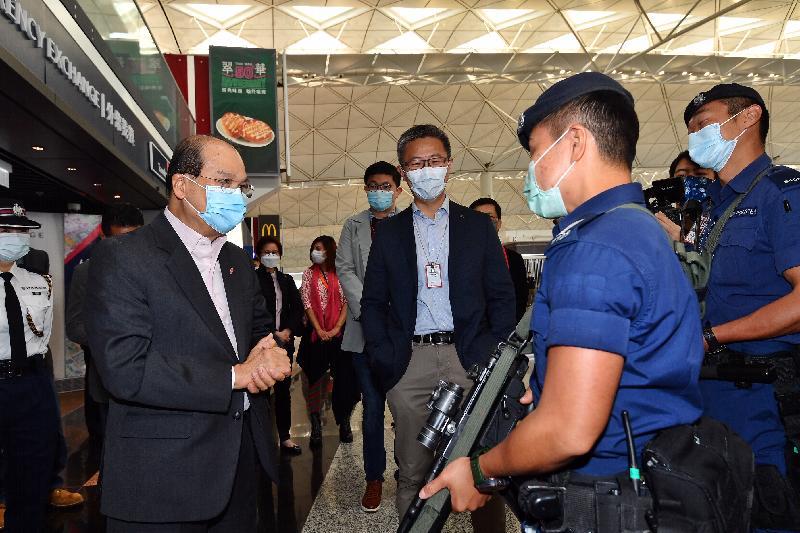 政務司司長張建宗今日(二月十三日)到訪香港國際機場。圖示張建宗(左一)在警務處副處長(行動)蕭澤頤(右三)陪同下探訪當值的警務處前線人員,了解他們的工作情況,向他們送上新年祝福。