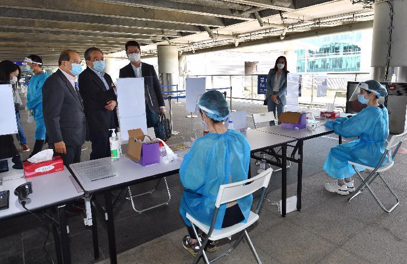 政務司司長張建宗今日(二月十三日)到訪香港國際機場。圖示張建宗(左一)參觀專為機場員工而設的專屬檢測中心,了解中心的運作情況。