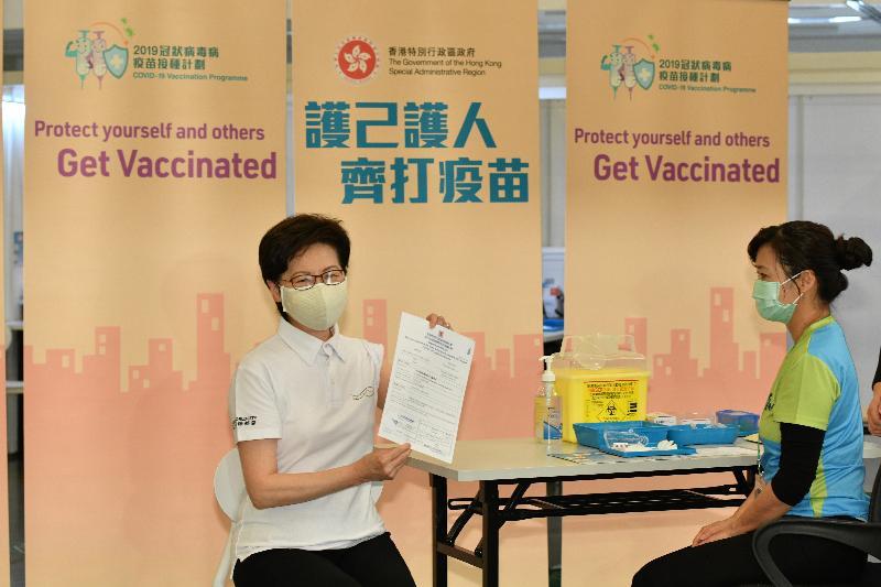 行政長官林鄭月娥與多名司局長今日(二月二十二日)到設於香港中央圖書館展覽館的社區疫苗接種中心接種新冠疫苗。圖示林鄭月娥(左)與疫苗接種紀錄。