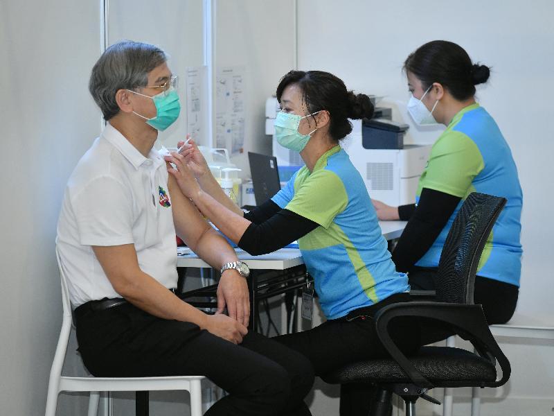 勞工及福利局局長羅致光博士(左)今日(二月二十二日)到設於香港中央圖書館展覽館的社區疫苗接種中心接種新冠疫苗。