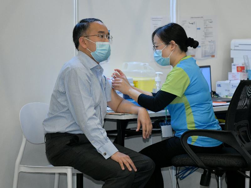 財經事務及庫務局局長許正宇(左)今日(二月二十二日)到設於香港中央圖書館展覽館的社區疫苗接種中心接種新冠疫苗。