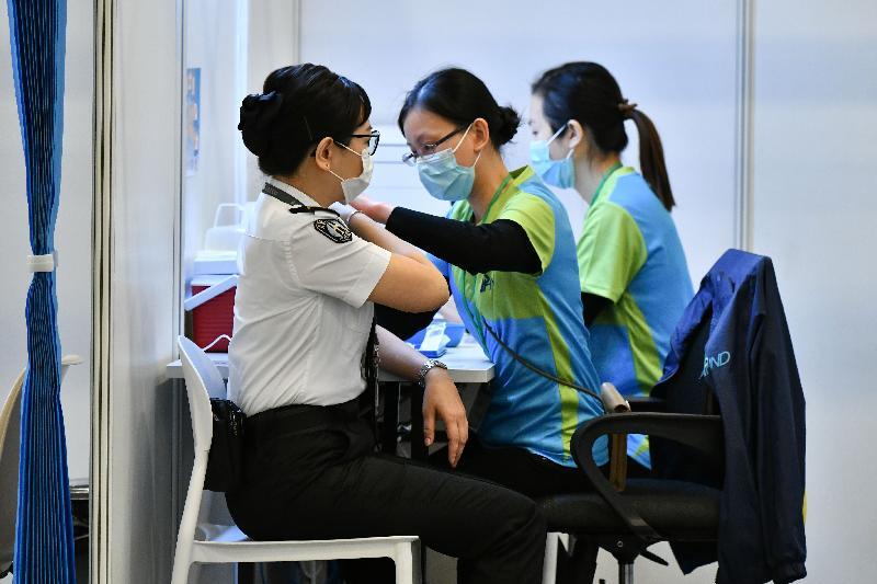 約二百名優先接種組別人士今日(二月二十三日)率先在設於香港中央圖書館展覽館的社區疫苗接種中心接種新冠疫苗,圖示一名機場工作人員接種疫苗。