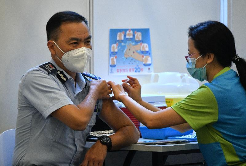 政府飛行服務隊總監胡偉雄機長(左)今日(二月二十三日)到設於香港中央圖書館展覽館的社區疫苗接種中心接種新冠疫苗。