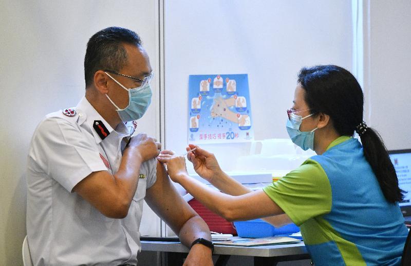 消防處處長梁偉雄(左)今日(二月二十三日)到設於香港中央圖書館展覽館的社區疫苗接種中心接種新冠疫苗。