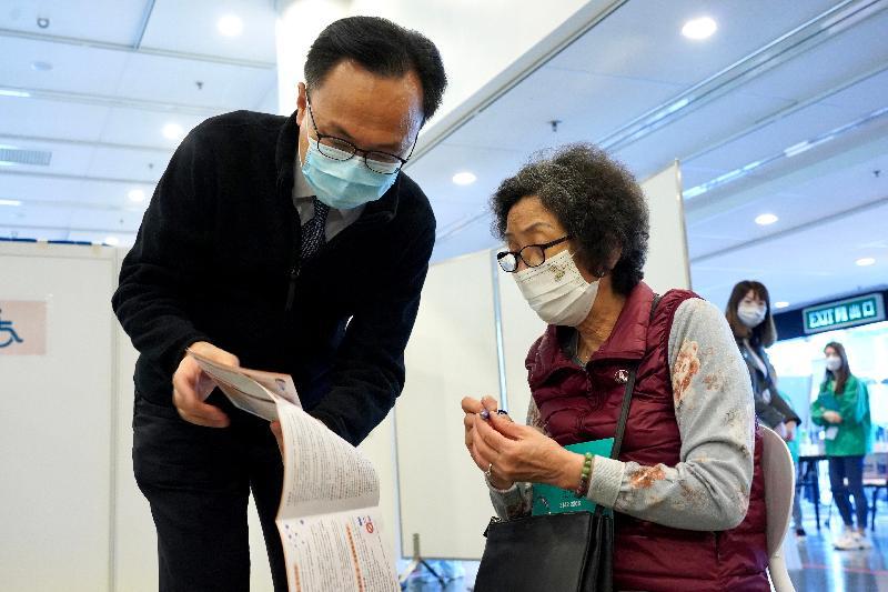 約二百名優先接種組別人士今日(二月二十三日)率先在設於香港中央圖書館展覽館的社區疫苗接種中心接種新冠疫苗,公務員事務局局長聶德權到場視察,並與一名長者交談。