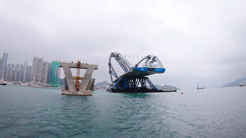Erection of the prefabricated double-arch steel bridge for the Cross Bay Link, Tseung Kwan O, was completed today (February 26). Photo shows the semi-submersible barge carrying the double-arch steel bridge at a position 30 metres from the bridge piers for final preparation.