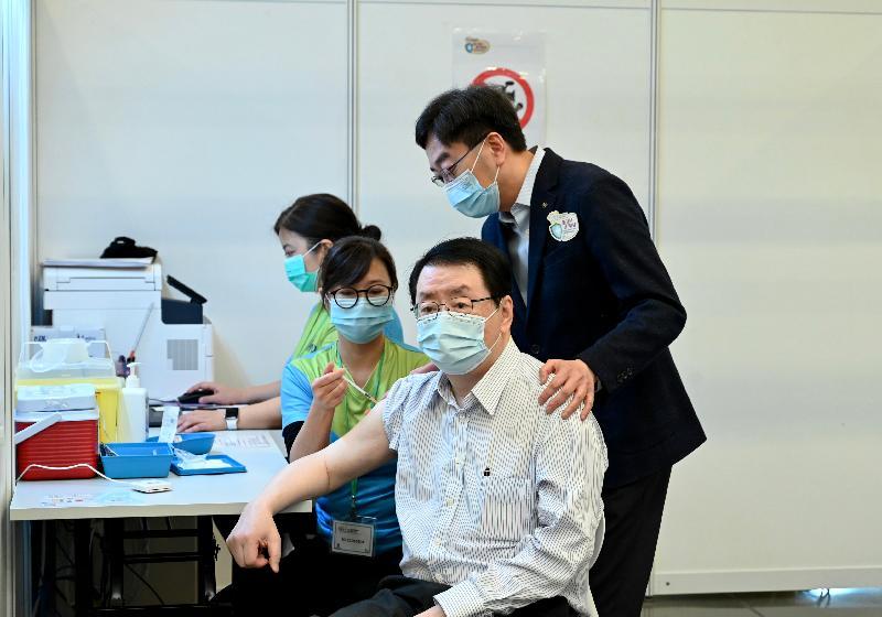 2019冠狀病毒病疫苗接種計劃今日(二月二十六日)正式展開。前衞生署署長林秉恩醫生(右二)在設於香港中央圖書館展覽館的社區疫苗接種中心接種新冠疫苗。前食物及衞生局局長高永文(右一)到場支持。