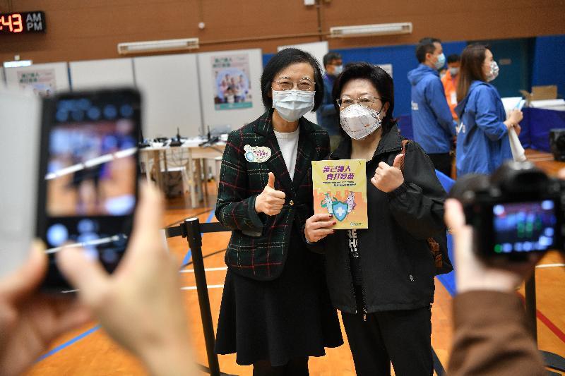 食物及衞生局局長陳肇始教授(左)今日(二月二十六日)在官涌體育館社區疫苗接種中心視察時,與市民合照。