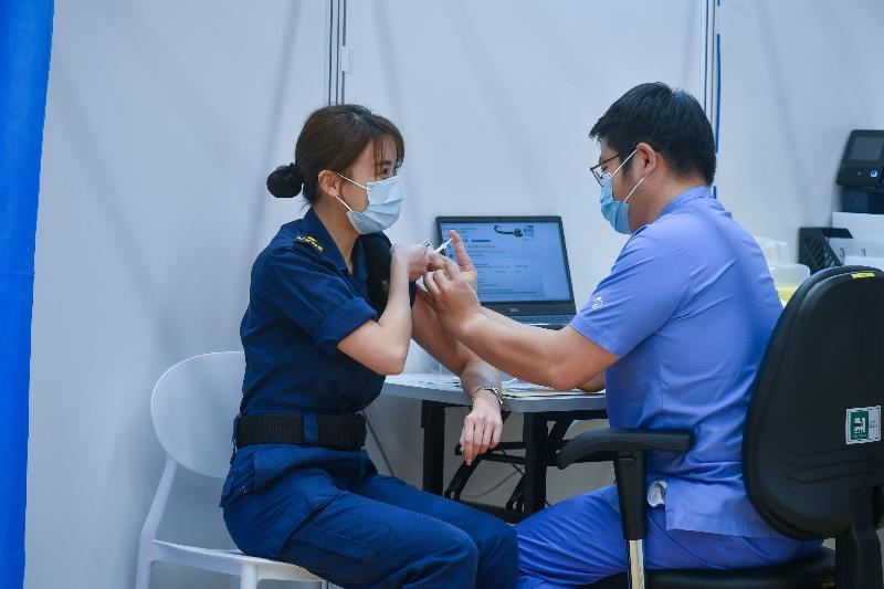 約一百名優先接種組別人士今日(三月八日)在設於中山紀念公園體育館的社區疫苗接種中心接種復必泰疫苗。圖示一名海關人員(左)接種疫苗。