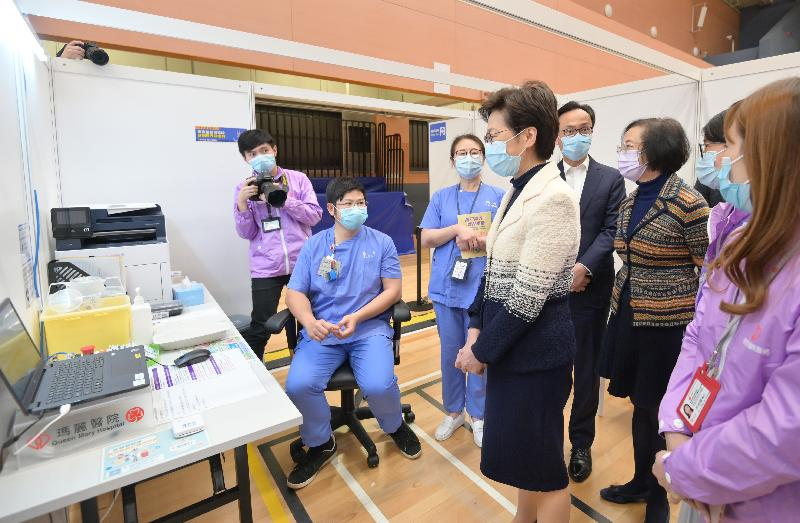 The Chief Executive, Mrs Carrie Lam, today (March 10) visited the Community Vaccination Centre at Sun Yat Sen Memorial Park Sports Centre. Photo shows Mrs Lam (fourth right) being briefed by the healthcare workers on the operation of the centre. Looking on are the Secretary for the Civil Service, Mr Patrick Nip (fifth left) and the Secretary for Food and Health, Professor Sophia Chan (sixth left).