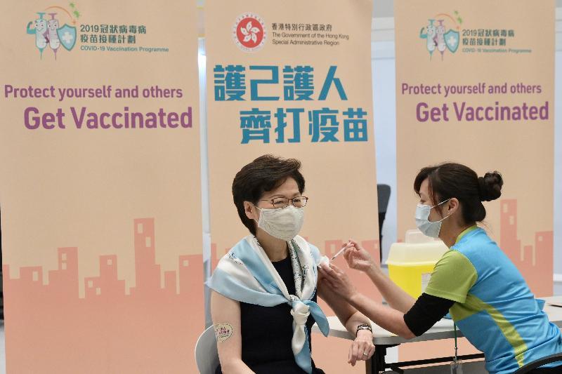 行政長官林鄭月娥今日(三月二十二日)上午聯同多名司局長在添馬政府總部會議廳接種第二劑新冠疫苗。圖示林鄭月娥(左)接種疫苗。