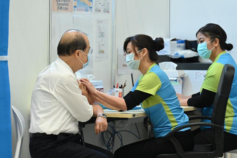 行政長官林鄭月娥今日(三月二十二日)上午聯同多名司局長在添馬政府總部會議廳接種第二劑新冠疫苗。圖示政務司司長張建宗(左一)接種疫苗。