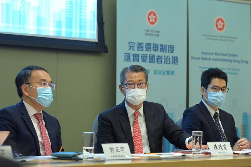 財政司司長陳茂波今日(四月一日)會見商界和會計界代表,解說有關全國人民代表大會常務委員會為落實《全國人民代表大會關於完善香港特別行政區選舉制度的決定》就《基本法》附件一《香港特別行政區行政長官的產生辦法》和附件二《香港特別行政區立法會的產生辦法和表決程序》的新修訂內容。圖示陳茂波(中)在其中一場會面發言。財經事務及庫務局局長許正宇(左)和財經事務及庫務局副局長陳浩濂(右)亦有出席。
