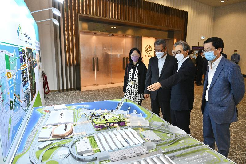 財政司司長陳茂波今日(四月十二日)視察香港國際機場及機場三跑道系統的工地,了解香港機場管理局(機管局)各主要項目的進展。圖示陳茂波(左二)聽取機管局主席蘇澤光(右二)講解「航天城」項目的進展。旁為運輸及房屋局常任秘書長(運輸)陳美寶(左一)及機管局行政總裁林天福(右一)。