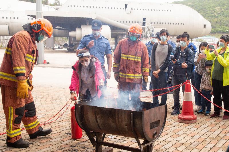 消防處今日(四月十五日)在消防及救護學院舉行開放日。圖示消防人員教導市民使用滅火筒的方法,以提高市民對消防安全的意識。