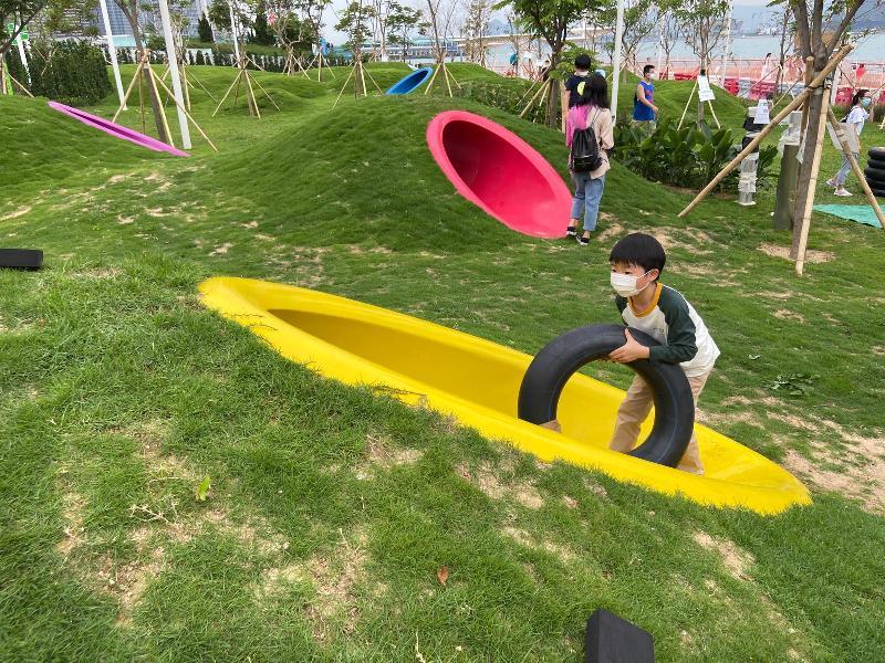 連接金鐘添馬和香港會議展覽中心的灣仔海濱長廊今日(五月七日)進一步開放,長廊靠近添馬公園的一端,設置了一個以「童樂園」為主題的活動區,藉着園境設計、高低起伏的草坪,配以色彩鮮艷的渠桶,於鬧市中營造天然風格的自由活動空間。