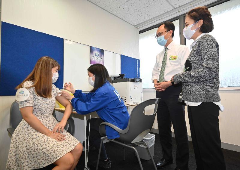 公務員事務局局長聶德權(右二)和華人置業集團行政總裁陳凱韻(右一)今日(六月二十八日)視察華人置業集團員工和租戶等透過政府外展服務接種復必泰疫苗的情況。圖示一名員工(左一)接種新冠疫苗。
