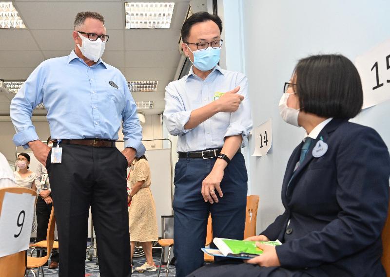 公務員事務局局長聶德權今日(七月五日)到訪香港迪士尼樂園,在香港迪士尼樂園度假區行政總裁莫偉庭的陪同下,了解主題公園職員透過政府外展服務接種新冠疫苗的情況。圖示聶德權(中)和莫偉庭(左)與完成接種疫苗的餐飲部員工交談。