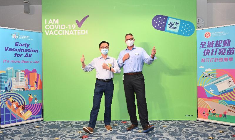 公務員事務局局長聶德權今日(七月五日)到訪香港迪士尼樂園,在香港迪士尼樂園度假區行政總裁莫偉庭的陪同下,了解主題公園職員透過政府外展服務接種新冠疫苗的情況。圖示聶德權(左)和莫偉庭(右)一同支持2019冠狀病毒病疫苗接種計劃。