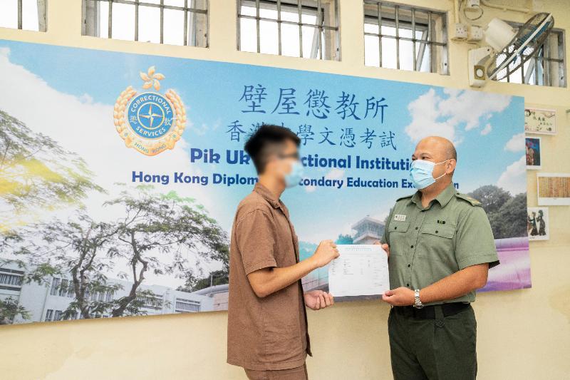 今年共有七名青少年在囚人士報考香港中學文憑考試。圖示壁屋懲教所監督朱遠明(右)頒發香港中學文憑考試成績通知書予青少年在囚人士。